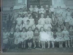 Danny as a child (top row, second from the right) with his classmates.